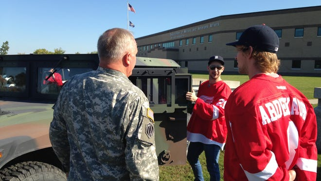 Former Michigan State star Justin Abdelkader, right, watches as Tomas Tatar opens the door to a Humvee on Wednesday during the Detroit Red Wings' sixth annual MI Wings Community Tour at the Michigan National Guard Joint Forces Headquarters in Lansing.