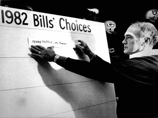 Buffalo Bills head coach Chuck Knox places Perry Tuttle's name atop the Bills' draft choice tote board after he was selected as the 19th player taken in the NFL draft in 1982