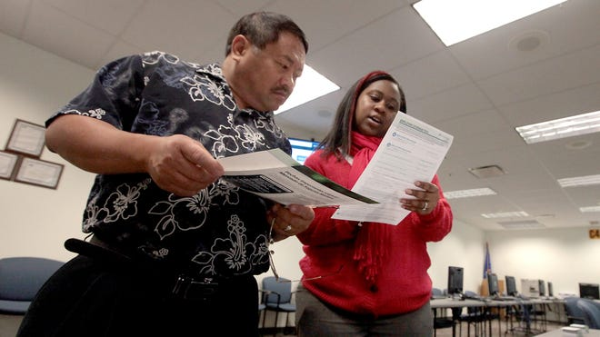 Chongtou Yang, 59, of Cottage Grove, Wis.,  receives guidance on new health insurance exchanges during a visit with counselor Lorraine McGowan at the Dane County Job Center in Madison, Wis., on Oct. 1.