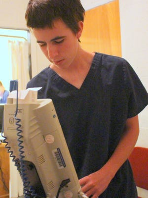 Sophomore Isaiah Granado, a nurse assistant at Deming High School, checks the function on a blood pressure monitor.