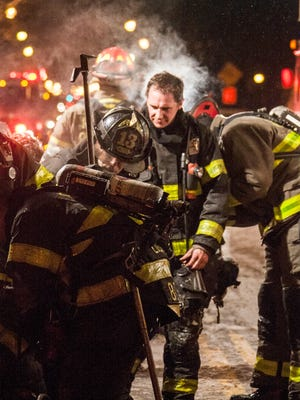 Firefighters change air bottles in sub freezing temperatures at a house fire on Chili Avenue Tuesday night.