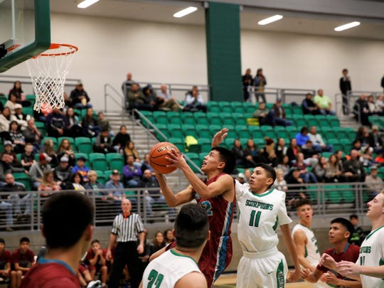 Shiprock's Arron Lee, No. 22 in maroon, attacks the lane through heavy traffic and scores a layup during a non-district game on Thursday, Jan. 4 at Farmington High. The Chieftains are handling their own against tougher competition this season.