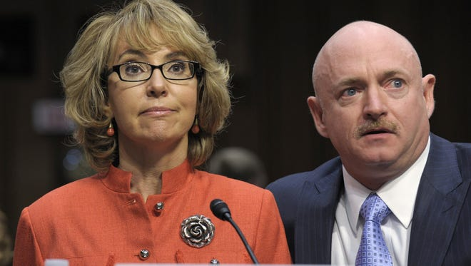 Former Arizona Rep. Gabrielle Giffords, who was seriously injured in the mass shooting that killed six people in Tucson, Ariz., in 2011, sits with her husband, Mark Kelly,  on Capitol Hill in 2013, where she delivered remarks on gun violence.