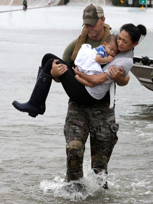Houston Police SWAT officer Daryl Hudeck carries Catherine Pham and her 13-month-old son Aiden after rescuing them from their home surrounded by floodwaters from Tropical Storm Harvey Sunday, Aug. 27, 2017, in Houston. (AP Photo/David J. Phillip)