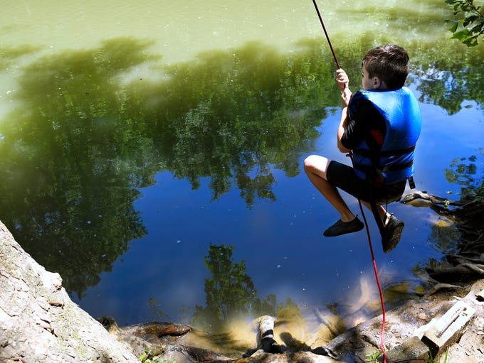 Flynn Whelan, 10, uses a rope swing to jump into the