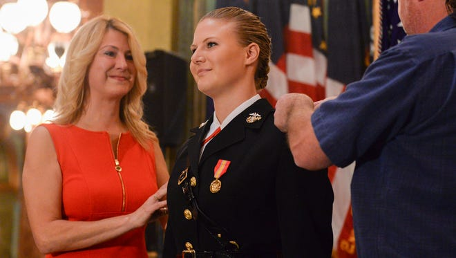 Marine Corps 2nd Lt. Elizabeth Vincent gets her gold bars pinned on her by her mother, Jennifer Kie,l and her father, Stacy Vincent, during Elizabeth's commission ceremony Friday at the state Capitol.