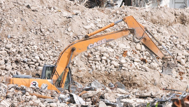 A Renascent employee makes his way through piles of rubble on the property of the former Reid Hospital in Richmond.