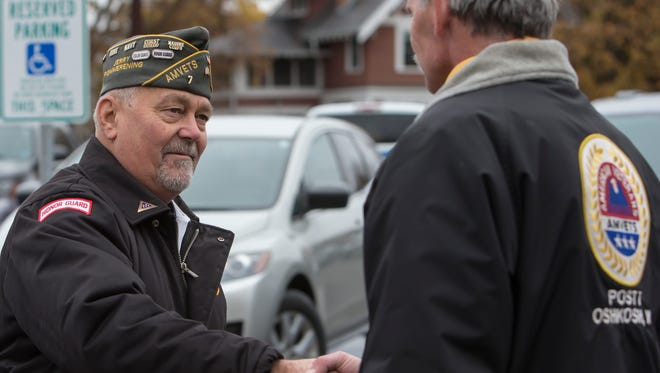 Jerry Pommerening greets other vets in the Winnebago County courthouse parking lot before the Veterans Day ceremony November 11, 2014.