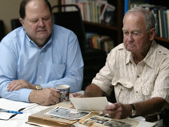 Jim Roy, left, and his step-father Robert Lowe look through a scrapbook of photos and newspaper clippings Monday at the 232-HELP offices in Lafayette. Jewell Lowe, Roy's mothers and Lowe's late wife, was the founder of 232-HELP.By Leslie WestbrookAugust 13, 2012