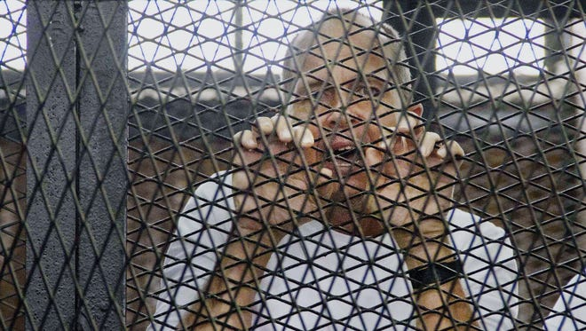 Al-Jazeera's award-winning Australian correspondent Peter Greste, appears in a defendants' cage in a courthouse near Tora prison in Cairo on May 3.