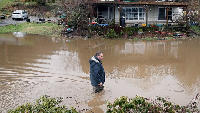 Pal Kolek walks Thursday in his flooded front yard along Southworth Drive in South Kitsap. The nearby culvert was overwhelmed with the rain and melting snow.