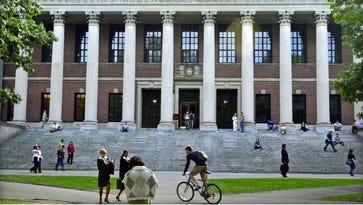 Students pass in front of Harvard's Widener Library on October 10, 2003, in Cambridge, Massachusetts.