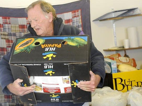 Volunteer Jeff Webb carries a box loaded with food.