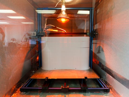 A 3D printer churns out parts for a robot at Slate Robotics on Tuesday, July 17, 2018.