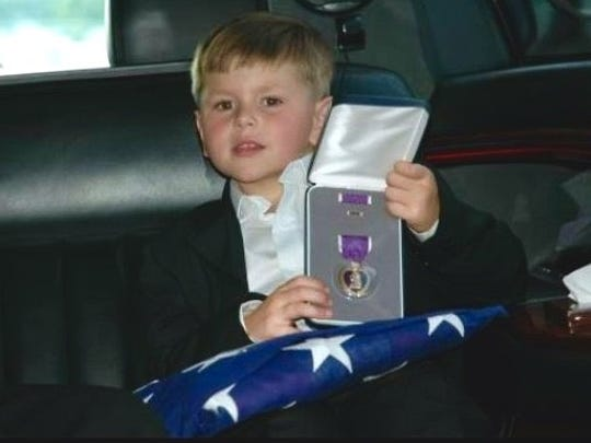 Hunter Youngblood just after the funeral with his father's purple heart and 'Daddy's Flag.'