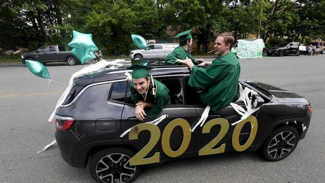 Abington High School seniors Tom Furness, Bubba Gendreau and Jake Bennett hang out of their car while seniors are celebrated during a parade. Wicked Local Staff Photo/Robin Chan