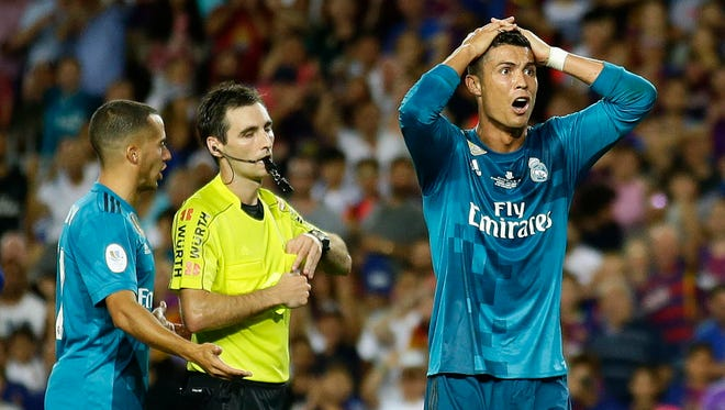 Real Madrid's Cristiano Ronaldo, right, reacts after Referee Ricardo de Burgos shows a yellow card during Saturday's match against Barcelona.