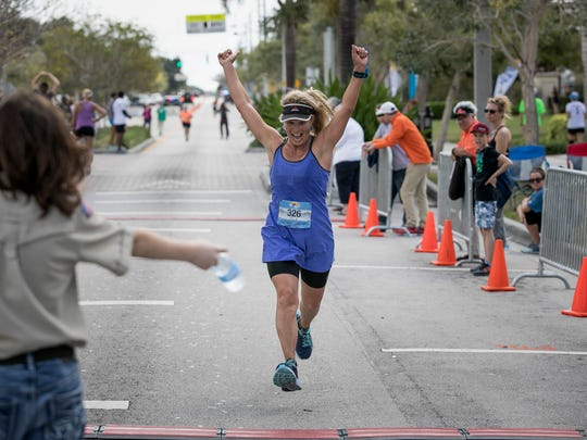 Paula Jean Lunt of Tenants Harbor, Maine, throws her hands in the air as she crosses the finish line during the Marathon of the Treasure Coast in Stuart March 5, 2017. Lunt finished with a time of 3:52:48.4.
