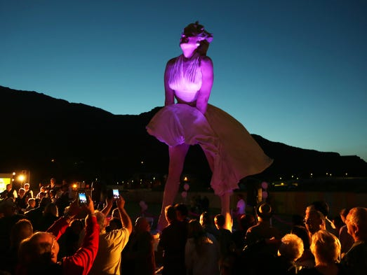 Somber lighting illuminates the Forever Marilyn statue as hundreds gather in downtown Palm Springs to bid farewell to  Forever Marilyn Thursday, March 27, 2014. The statue will be removed next week.