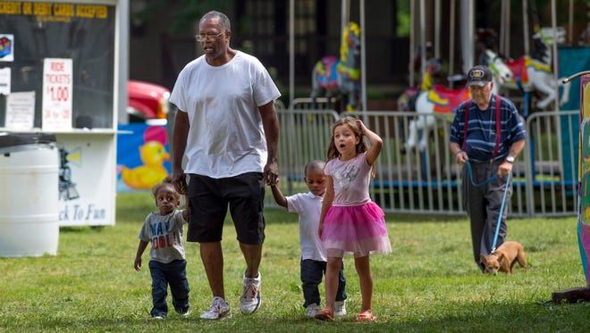 Greg Fox of Rockport, Ind., and his young crew, grandson Jarvis Lindsey Jr., 2, left, Adonis Shields Jr., 2, and step granddaughter Kylie Robbins, 5, arrive early to Boom Fest before the rides opened Thursday afternoon. They figured they might as well eat until the rides got going.