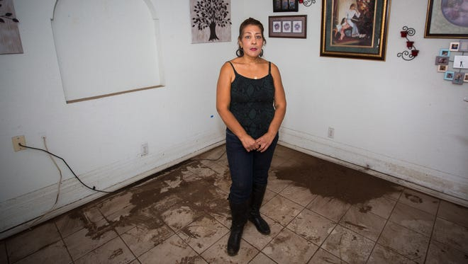 Diane Terrell stands in the living room of her rented house off of Third Street, June 22, 2016. Much of Terrell's property had to be removed from the home after a broken water main flooded the home.