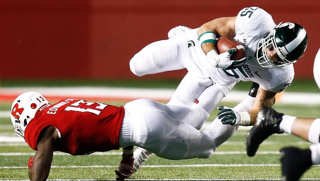 Michigan State's Joe Bachie jumps over Rutgers' Gus Edwards during MSU's 40-7 win on Saturday, Nov. 25, 2017, in Piscataway, N.J.