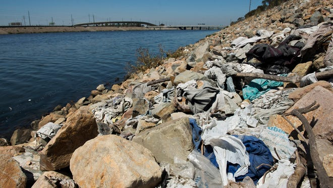 This Tuesday, Sept. 2, 2014 file photo shows a large pile of washed-up trash, including old plastic bags, sits alongside the Los Angeles River in Long Beach, Calif.