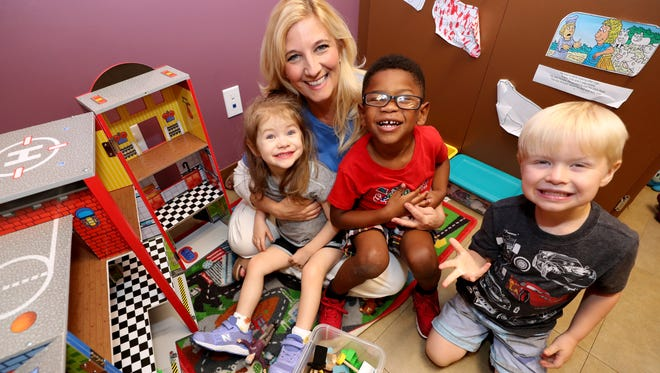 Co-founder Carrie Goodwin of Special Kids Therapy & Nursing Center is surrounded by some of the kids that are in the nursing care program (left to right) Holland, Bryson and Sebastian, on Tuesday, Aug. 7, 2018. The Special Kids Therapy & Nursing Center will be celebrating it's 20th anniversary this year.