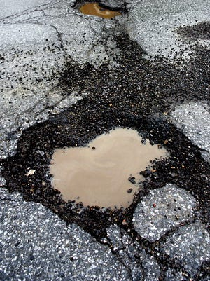 Potholes are caused by the repeated freezing and thawing of water on roads.
