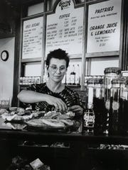 Judith Corlett, proprietor of the Dancing Goat coffeehouse in downtown Lansing, stocks her pastries in her newly opened coffee shop, June 1994.