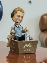 A P.J. Fleck bobblehead sits on the corner of the desk
