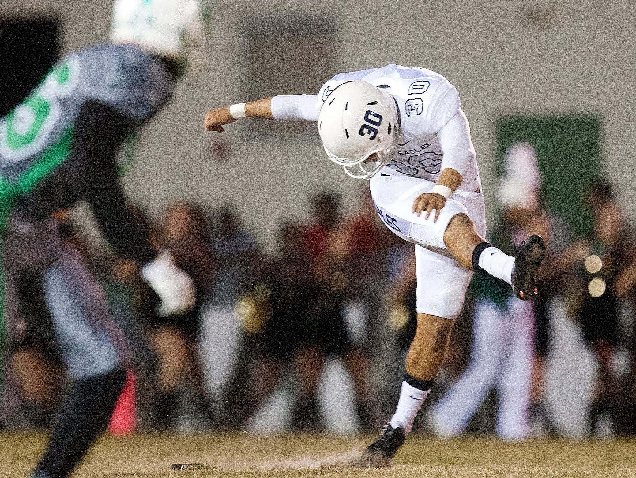 Naples High School's Jerry Nunez kicks off against Fort Myers on Friday (11/20/15) in the Region 6A-3 semifinals at Edison Stadium in Fort Myers. Naples beat Fort Myers 37-26.
