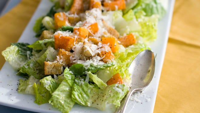 A plate of butternut Caesar salad with romaine lettuce and roasted cubes of butternut squash.