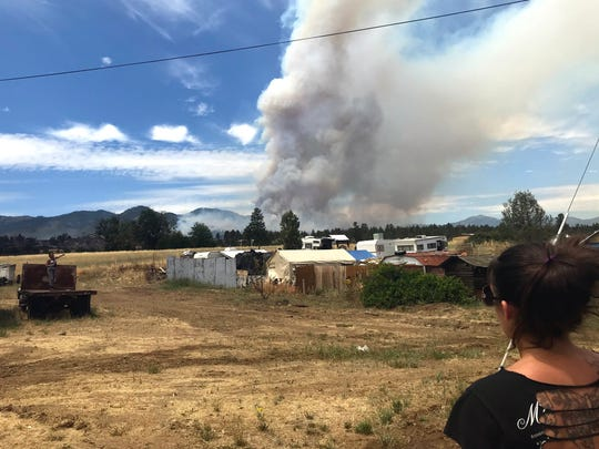 Erica Wilson watches a plume of smoke from the Klamathon Fire while at her father's home in Hornbrook.