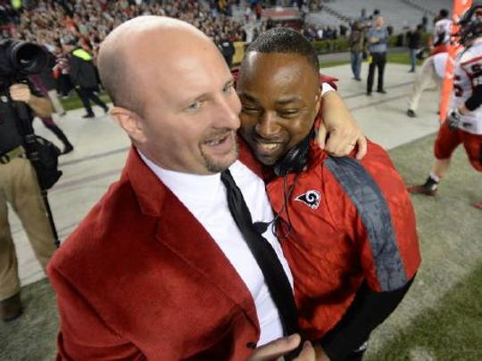 Hillcrest athletic director Tommy Bell, left, hugs football coach Greg Porter following the Rams' 2014 Class AAAA Division I state championship.