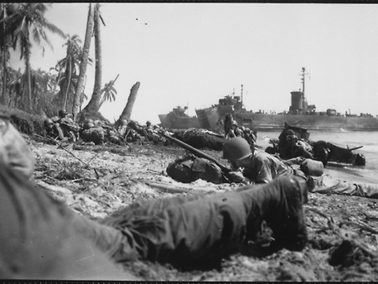 U.S. soldiers hug the sands of Leyte Island's beaches after rushing ashore from the landing barges of a Coast Guard-manned invasion transport.