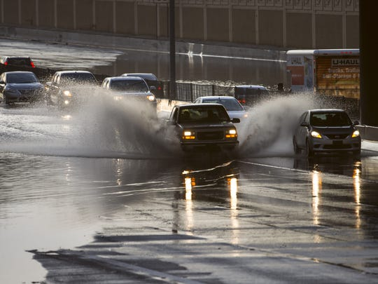 Cars make their way through one lane as the US 60 Highway flooded at Mill Ave. in Tempe, Ariz. on Aug. 3, 2017.