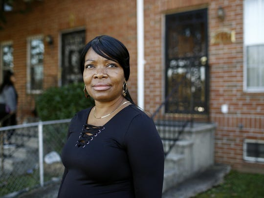 """Octavia Mason outside of her mother's home in Baltimore. Mason's drug use after a broken marriage caused her to lose her license to teach high schoolers to become pharmacy technicians. Now she participates in a program called """"Turnaround Tuesday"""" that helps people with criminal records, struggles with drug addiction, or simply a life of poverty find a living wage job."""