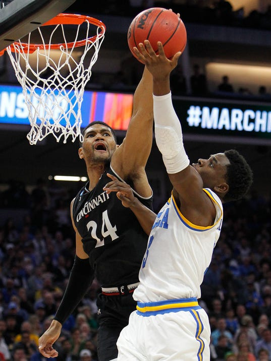 UCLA guard Aaron Holiday, right, goes to the basket against Cincinnati guard Jarron Cumberland during the first half of a second-round game of the NCAA men's college basketball tournament in Sacramento, Calif., Sunday, March 19, 2017. (AP Photo/Steve Yeater)