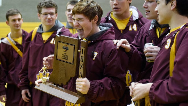 Joe Happe of Mater Dei carries the 2017 wrestling sectional championship trophy at Central High School in Evansville Saturday.  Mater Dei won their 41st consecutive sectional title Saturday.