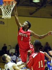 MOLLY BARTELS / COURIER & PRESS Bosse's JaQuan Lyle grabs the rim as he dunks against Memorial during a game at Memorial High School in 2012.