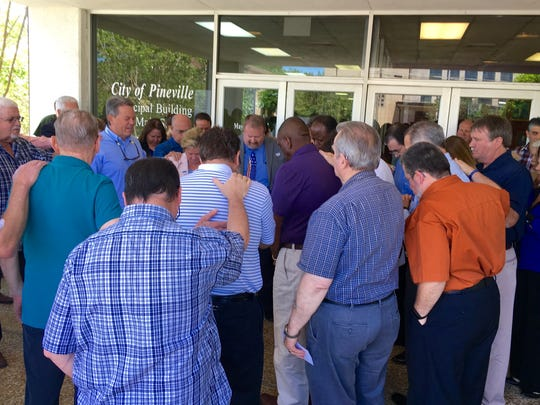 Members of the Pineville community pray Thursday for elected officials and public servants gathered at the center of the crowd at Pineville City Hall for National Day of Prayer.