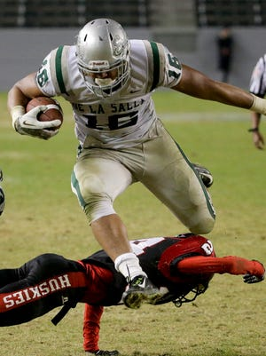 De La Salle's Devin Asiasi scores over the top of Centennial's Camryn Bynum during the second half of the CIF Open Division high school football championship game in Carson, Calif., Saturday, Dec. 20, 2014. De La Salle won 63-42.