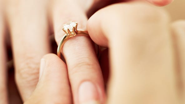 Close-up of a man's hand putting a diamond engagement ring a woman's finger.