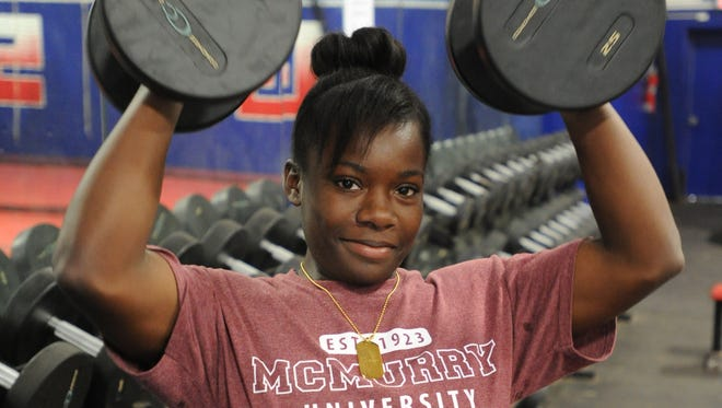 Cooper junior Tatiana Flowers poses with barbells in the school's weight room. Flowers, who won a region title in the 148-pound weight class earlier this month, will compete at the state powerlifting meet Friday, March 17, 2017 in Waco.