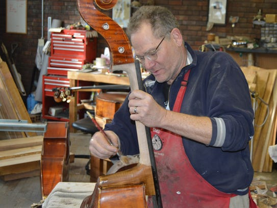Bassist/luthier Chris Roberts stains a new neck on a repaired bass at Cincinnati Bass Cellar in Westwood.