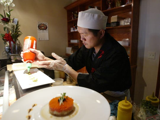 Owner Tony Yang applies a special sauce at his Fujiyama
