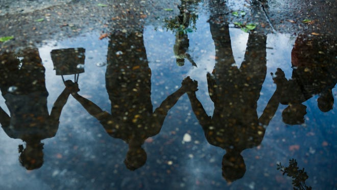 A reflection of Jefferson Davis's statue is seen in a puddle of water as protesters hold hands while surrounding the Confederate monument at Fourth Bluff Park in August.