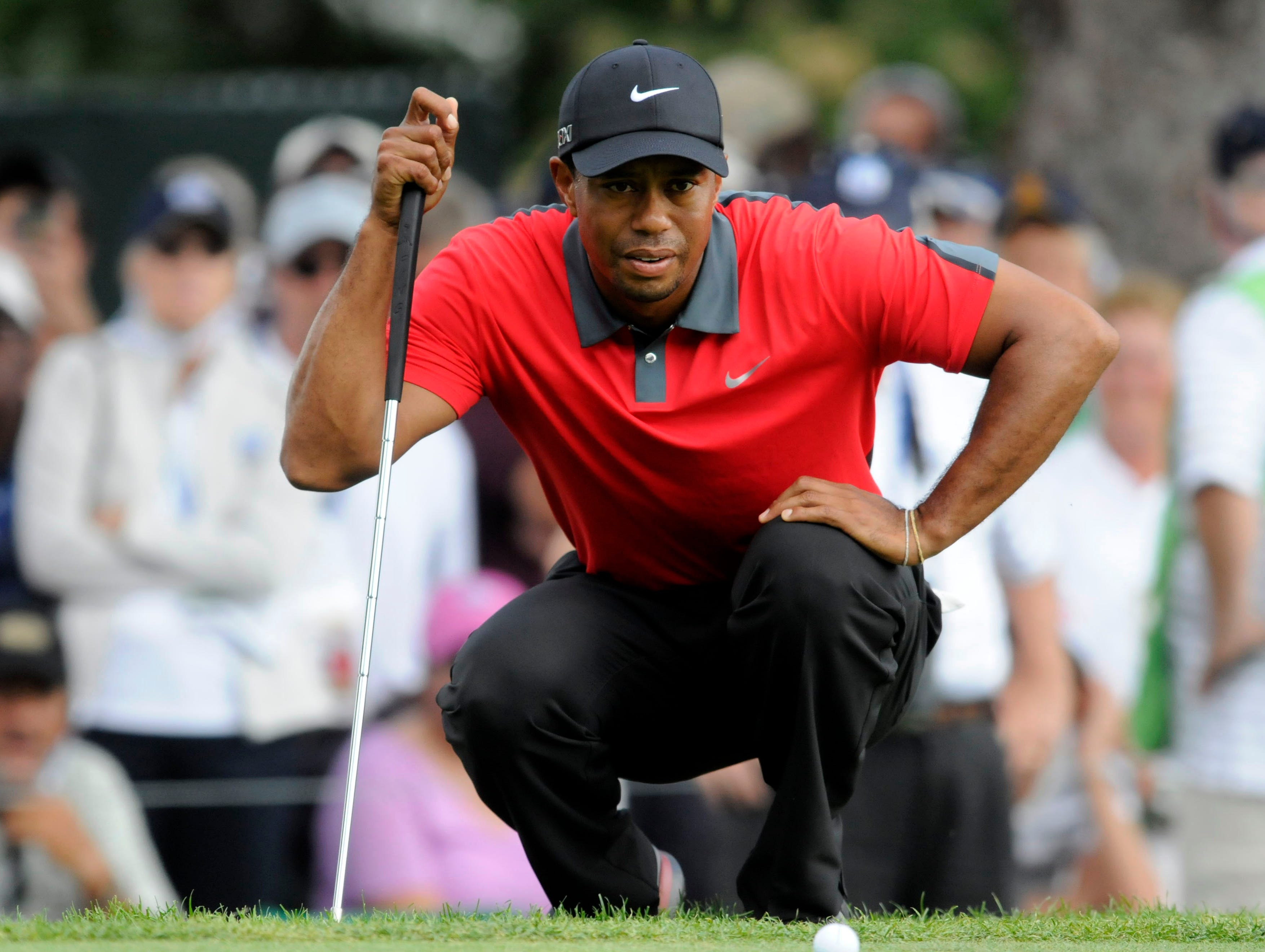 Tiger Woods lines up his putt at No. 9.