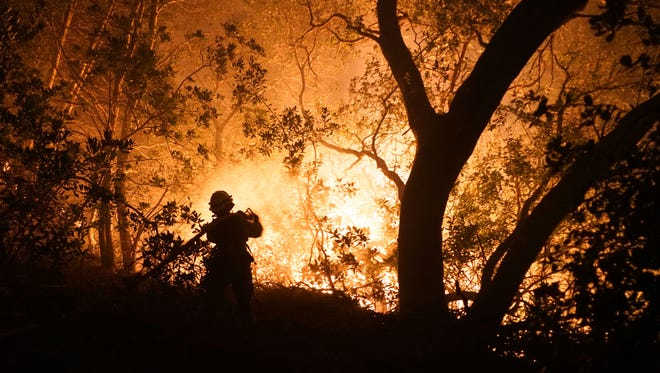 Firefighter Paige Madrid sprays down an approaching wildfire near Kenwood, Calif., on Oct. 10, 2017.